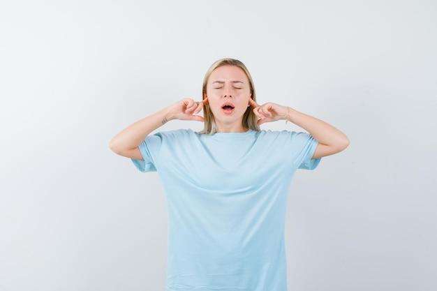 Mulher loira tapando as orelhas com o dedo indicador, mantendo a boca bem aberta