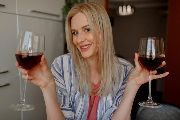 Mulher loira tases dois copos de vinho tinto em sua própria cozinha.