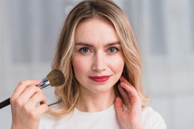 Mulher loira tendo maquiagem profissional