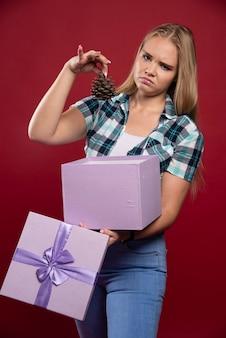 Mulher loira tira um cone de carvalho da caixa de presente e parece insatisfeita.