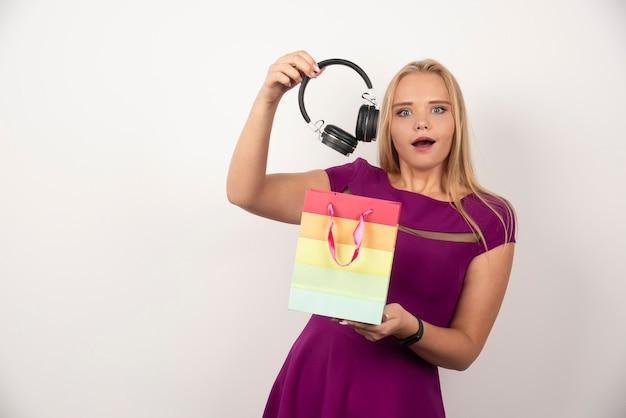 Mulher loira tirando fones de ouvido da bolsa com uma expressão feliz.