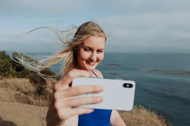Mulher loira tirando fotos com o telefone dela