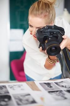 Mulher loira tirando fotos de seus projetos