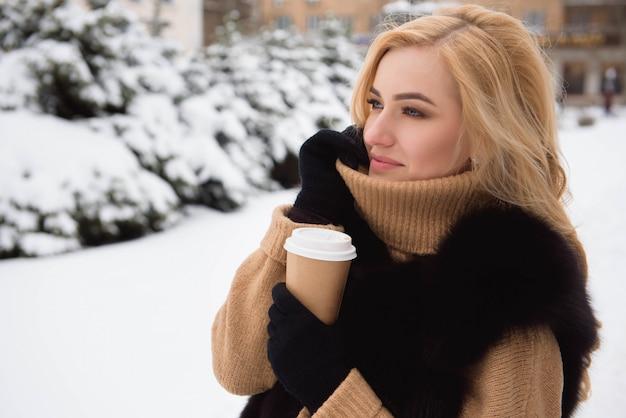 Mulher loira tomando café em winter park