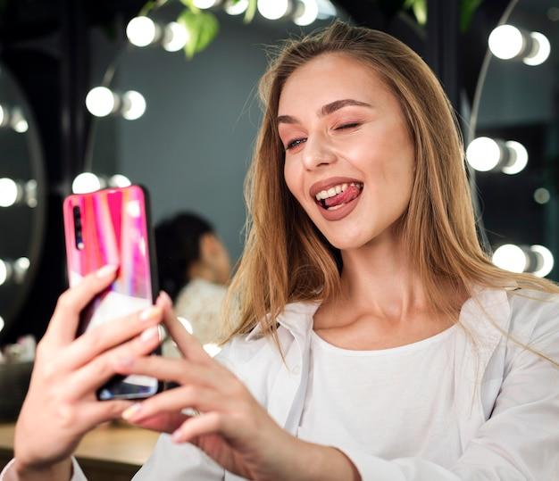 Mulher loira tomando uma selfie engraçada