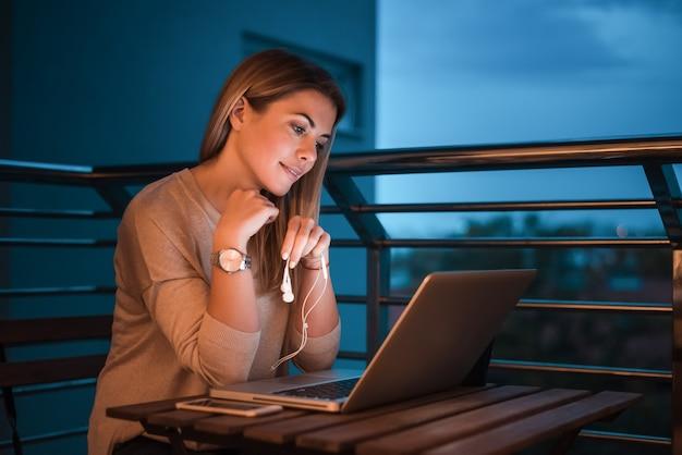 Mulher loira trabalhando no laptop à noite. imagem iso alta.