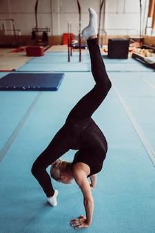 Mulher loira treinando para o campeonato de ginástica com vista lateral