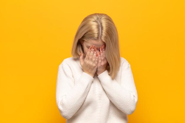 Mulher loira triste, frustrada, nervosa e deprimida, cobrindo o rosto com as duas mãos, chorando