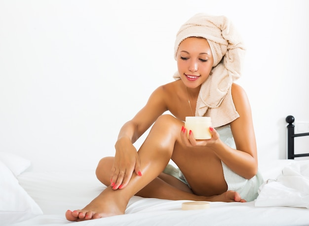 Mulher loira usando creme cosmético