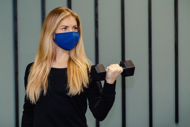 Mulher loira usando máscara facial, treinando no ginásio durante a pandemia.