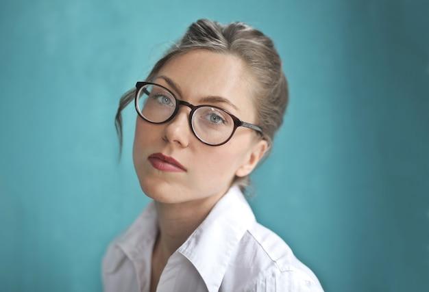 Mulher loira usando óculos ópticos e uma camisa branca
