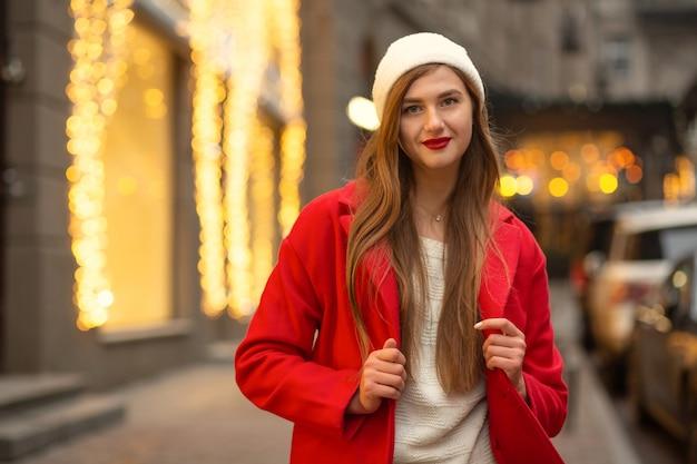 Mulher loira vestida casual com chapéu branco e casaco de inverno, caminhando na cidade. espaço para texto