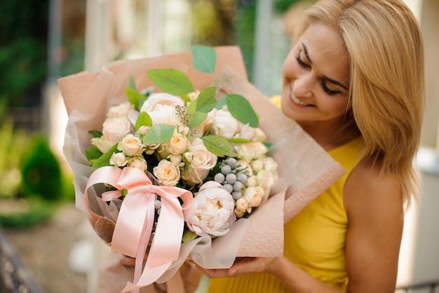 Mulher loira, vestida com um vestido amarelo, segurando um terno buquê de flores