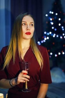 Mulher loira vestida de vermelho com uma taça de vinho branco ou champanhe em casa. árvore de natal. decorações de ano novo