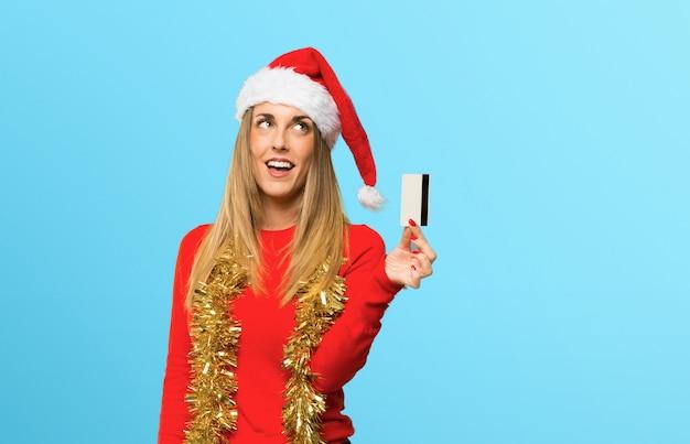 Mulher loira vestida para as férias de natal, segurando um cartão de crédito e pensando em fundo azul
