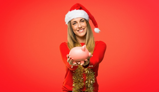 Mulher loira vestida para as férias de natal tomando um cofrinho e feliz