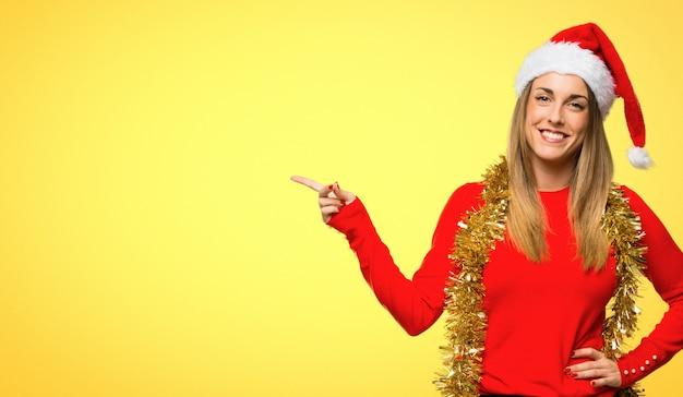 Mulher loira vestida para férias de natal, apontando o dedo para o lado