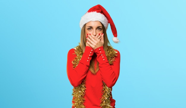 Mulher loira vestida para férias de natal, cobrindo a boca para dizer algo