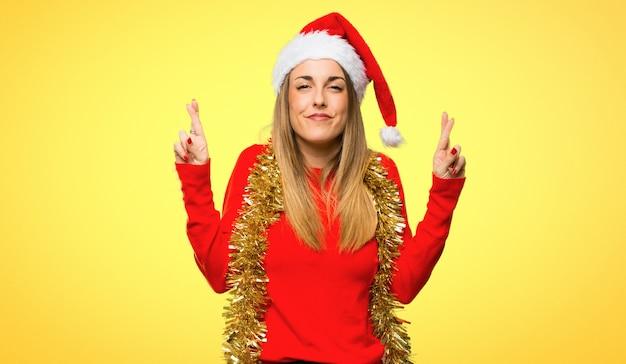 Mulher loira vestida para férias de natal com os dedos cruzando e desejando o melhor