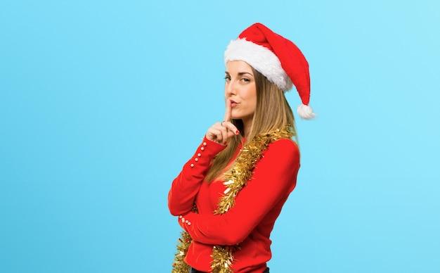 Mulher loira vestida para férias de natal, mostrando um sinal de fechar a boca