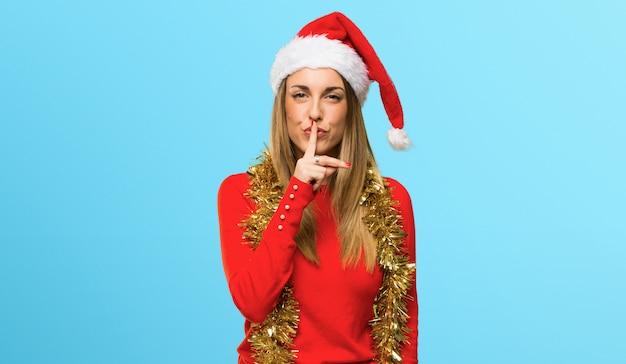 Mulher loira vestida para férias de natal, mostrando um sinal de silêncio gesto