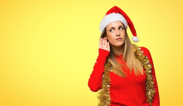 Mulher loira vestida para férias de natal ouvindo algo