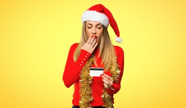 Mulher loira vestida para férias de natal, segurando um cartão de crédito e surpreso