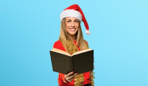 Mulher loira vestida para férias de natal, segurando um livro e dando a alguém