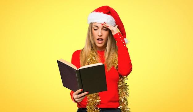 Mulher loira vestida para férias de natal, segurando um livro e surpreso enquanto desfruta
