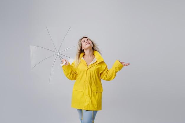 Mulher loira, vestindo capa de chuva amarela, segurando o guarda-chuva transparente, verificando o tempo se está chovendo