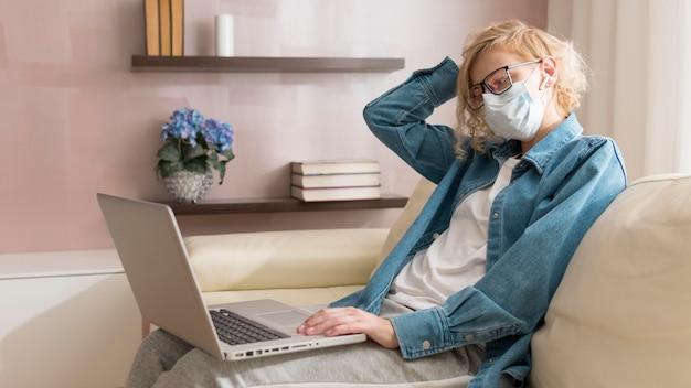 Mulher loira vestindo máscara e trabalhando