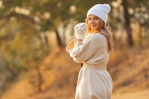 Mulher loira, vestindo um gorro branco lá fora