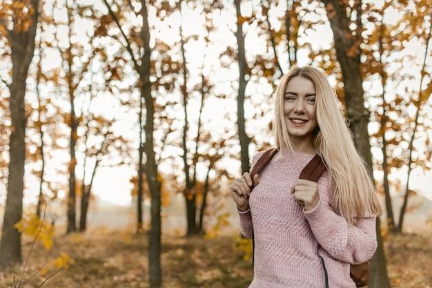 Mulher loira viajante posando nas costas da floresta de outono