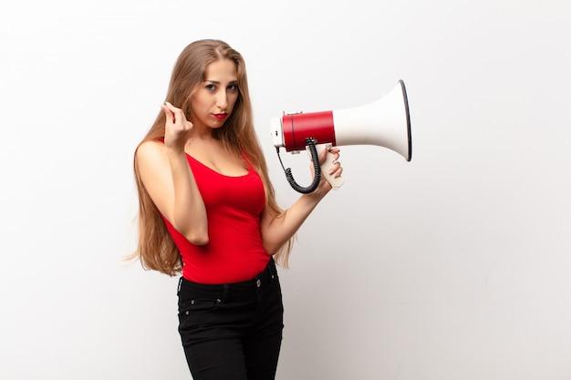 Mulher loira yound fazendo capice ou gesto de dinheiro, dizendo para você pagar suas dívidas! segurando um megafone