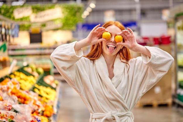 Mulher louca de roupão se divertindo com tangerinas, segurando mandarinas nos olhos, no supermercado, mostrando a língua