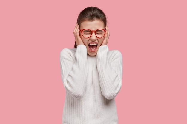 Mulher louca e desesperada cobre os ouvidos, grita com raiva, sendo emocional, irritada com barulho alto, usa roupa casual branca