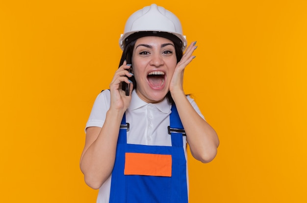 Mulher louca, feliz e animada jovem construtora em uniforme de construção e capacete de segurança falando no celular em pé sobre a parede laranja
