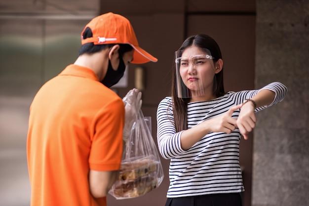 Mulher louca usando protetor facial mostra relógio para reclamar de atraso na entrega de comida