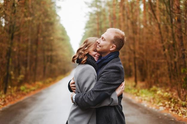 Mulher loura abraçando os ourtdoors marido