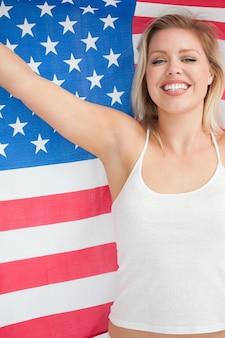 Mulher loura alegre que levanta a bandeira das estrelas e listras