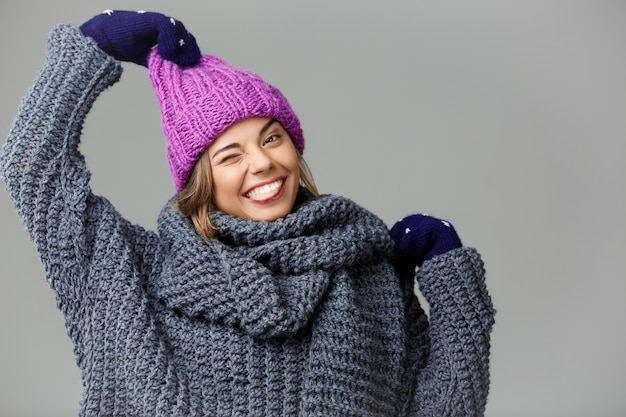 Mulher loura bonita engraçada nova na camisola knited do chapéu e luvas que sorriem no cinza.