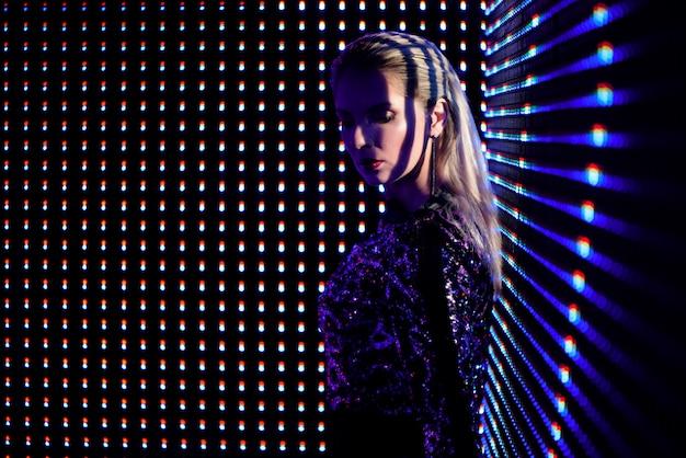 Mulher loura bonita no fato na moda que aprecia a vida noturno, menina lindo dentro na iluminação de néon.
