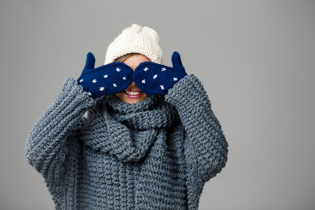 Mulher loura bonita nova na camisola e nas luvas tricotadas do chapéu que sorriem fechando seus olhos com as mãos no cinza.