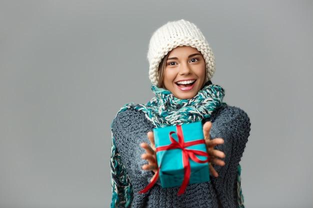 Mulher loura bonita nova na camisola e no lenço tricotados do chapéu que sorriem dando a caixa de presente no cinza.