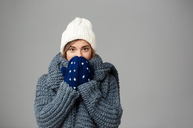 Mulher loura bonita nova na camisola knited do chapéu e luvas que sorriem no cinza.