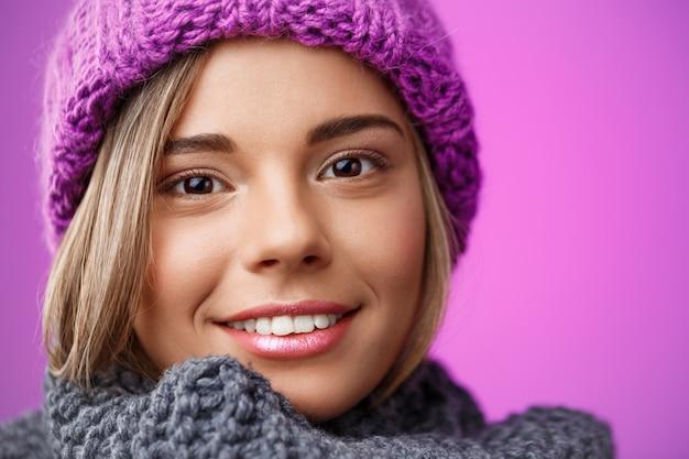 Mulher loura bonita nova no chapéu e na camisola knited que sorriem na violeta.