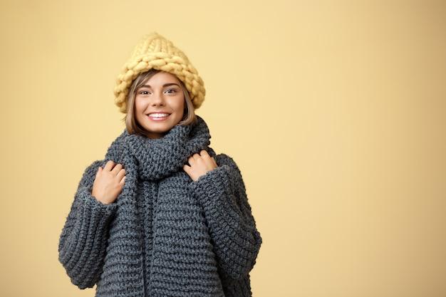Mulher loura bonita nova no chapéu e na camisola knited que sorriem no amarelo.