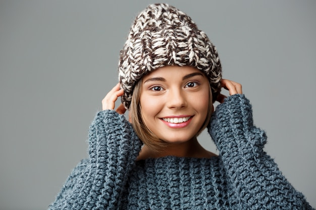 Mulher loura bonita nova no chapéu e na camisola knited que sorriem no cinza.
