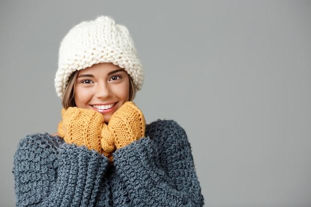 Mulher loura bonita nova no lenço da camisola do chapéu knited e nas luvas que sorriem no cinza.