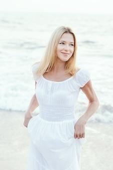 Mulher loura do turista maduro feliz atrativo no vestido branco longo na praia tropical da areia asiática.